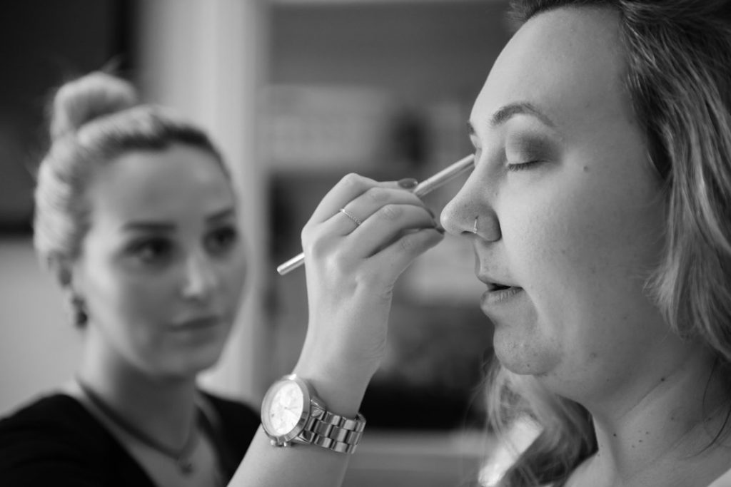Eye shadow being applied to the bride by the makeup artist