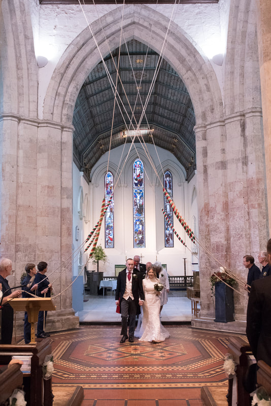 Bride and groom walking under church bells