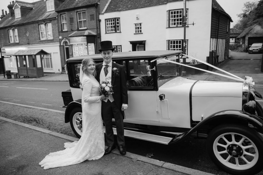 Bride and groom by the wedding car in hertfordshire