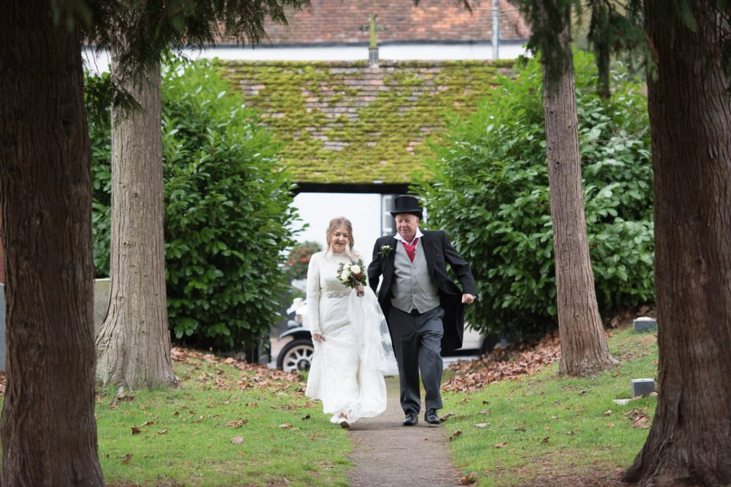 Father walking bride through the churchyard