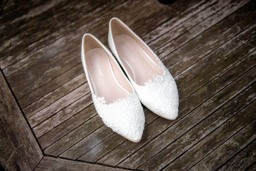 White Wedding shoes on a wooden table