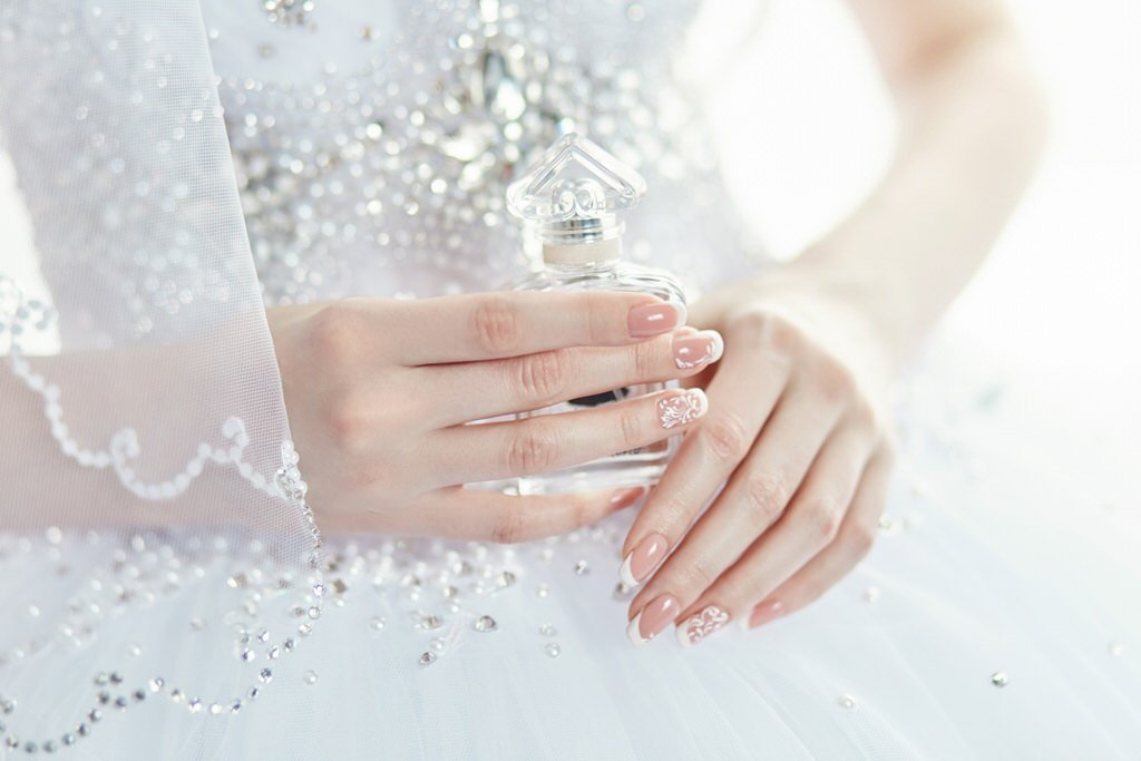 Perfume bottle in the hands of the bride. A woman is preparing for her wedding. Bride in elegant wedding dress, beautiful manicured hands