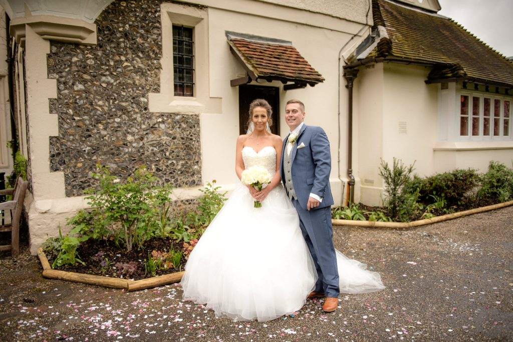 The bride and groom pose for a photo outside of the ware priory