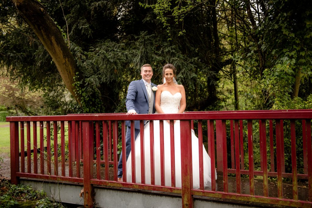 The bride and groom on a bridge at the ware priory
