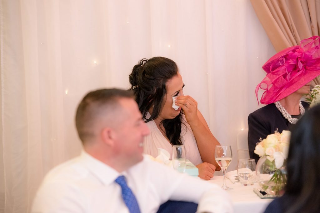 A bridesmaid wipes away tears of laughter