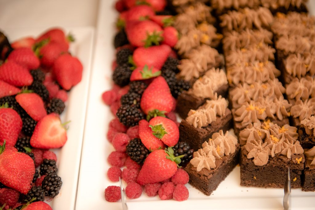 A plate of strawberries, berries and cakes