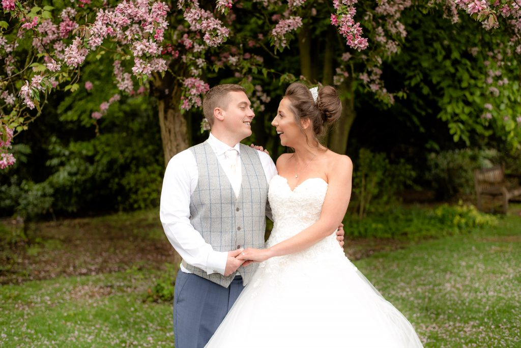 The bride and groom pose for a photo in the grounds of ware priory