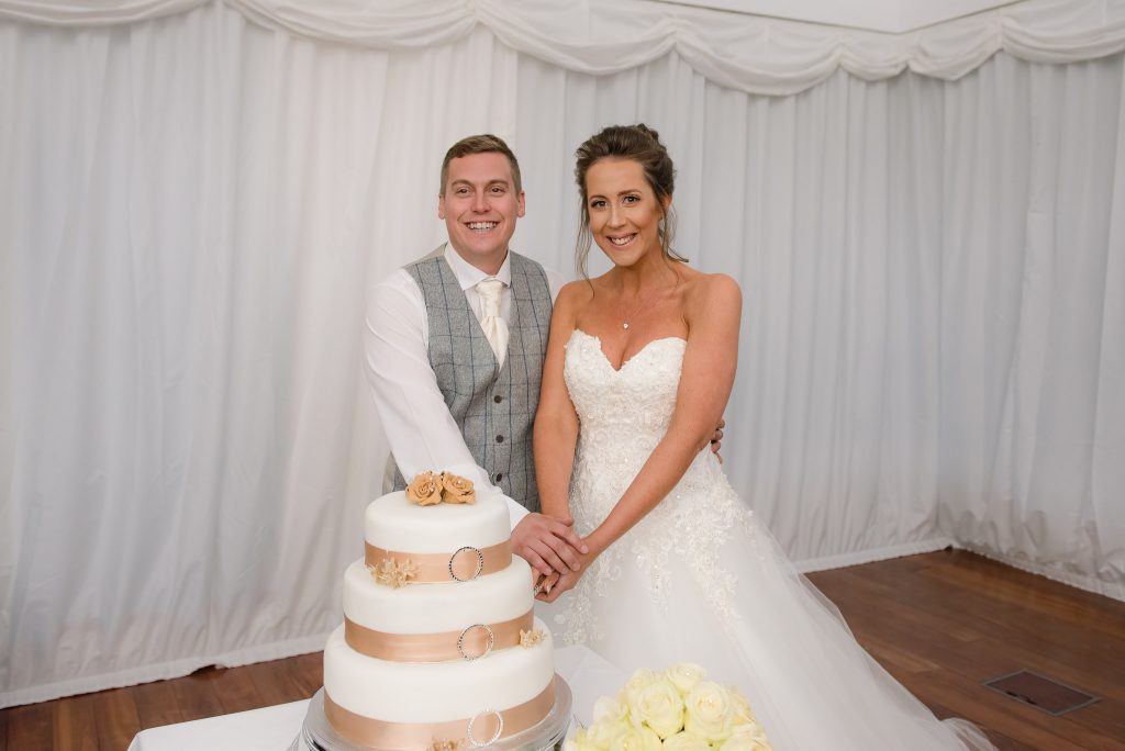 The bride and groom cut the cake at ware priory
