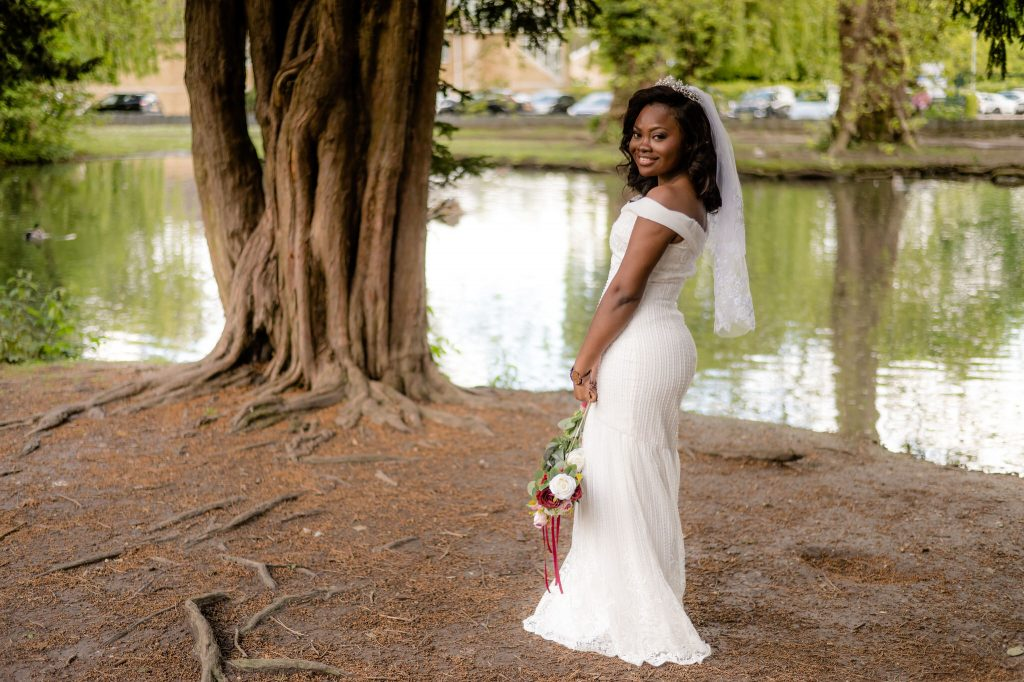 The bride poses beside the lake