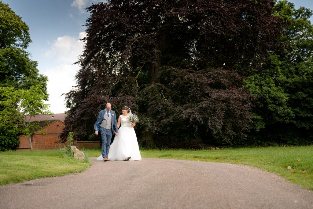 the bride and groom walk along hitchin priory
