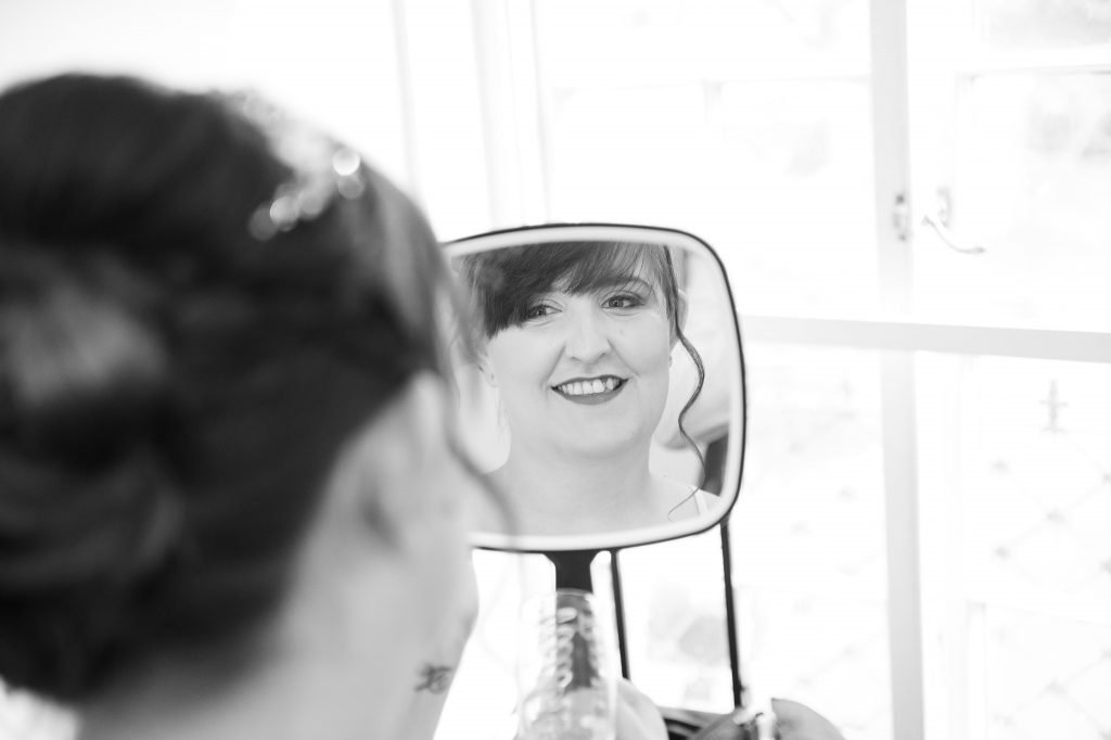 the bride checks out her makeup in the mirror
